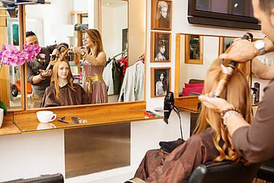 Hairdressers using curling tongs on customers long red hair in salon - p429m1407771 by Nancy Honey