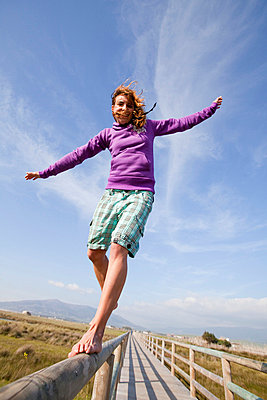 Young woman balancing barefoot on wooden structure   - p4429529f by Design Pics