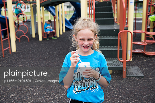 Smiling Curly Haired Girl Eats Slush on School Playground at Field Day - p1166m2191891 by Cavan Images