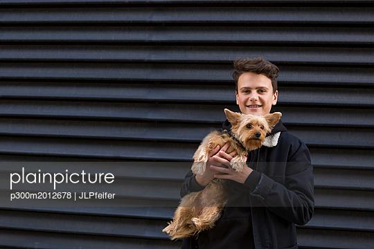 Portrait of smiling teenage boy with his dog against black background - p300m2012678 von JLPfeifer