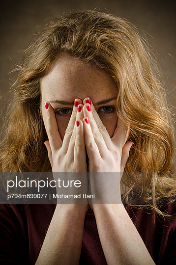 Young woman hiding face