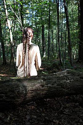 Frau sitzt im düsteren Wald - p045m953749 von Jasmin Sander