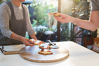 Couple enjoying fresh homemade pizza - p1023m2208352 by Sam Edwards