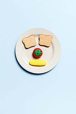 Face on plate made with bread, tomato and corn - p1094m1467628 by Patrick Strattner