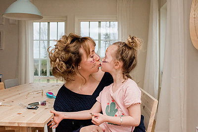 mother kissing daughter whilst they play with make up at home - p1166m2165840 by Cavan Images