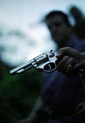 Hand hält Pistole, Personengruppe im Hintergrund - p1316m1160369 von Peter von Felbert