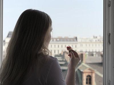 Frau mit Erdbeere blickt aus dem Fenster - p1383m1584332 von Wolfgang Steiner