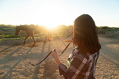 Spain, Tarifa, woman leading horse on riding ring at sunset - p300m2080665 by Sebastian Kanzler