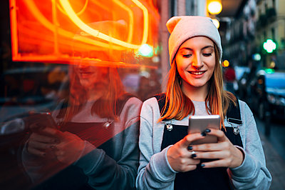 Smiling young woman standing next to neon light using her smartphone at night - p300m2144064 by Jose Luis CARRASCOSA