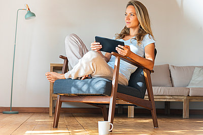 Contemplating woman holding digital tablet while sitting on armchair in living room - p300m2277497 by Steve Brookland