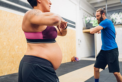 Pregnant woman and trainer warming up in gym - p429m2058480 by Eugenio Marongiu