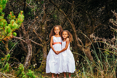 Mixed race sisters wearing dresses in garden - p555m1306260 by Inti St Clair