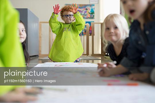 Portrait confident preschool boy with finger paints at poster - p1192m1560163 by Hero Images