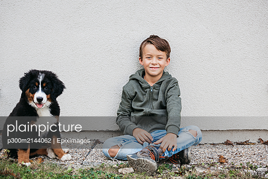 Boy playing with his Bernese mountain dog in the garden - p300m2144062 von Epiximages