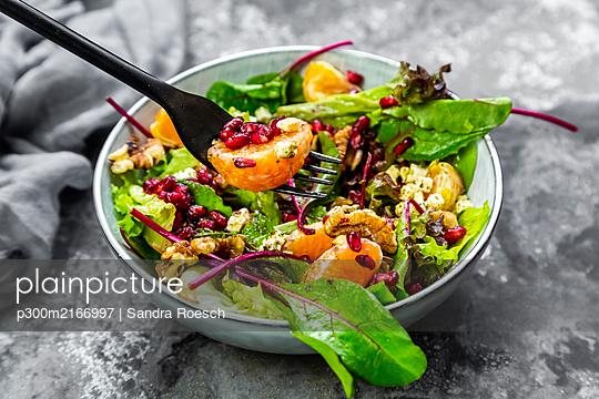 Wintersalat mit gemischten Blattsalat, Mandarinen, Walnüssen, Feta und Granatapfelkernen - p300m2166997 von Sandra Roesch