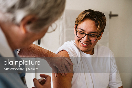 Smiling young male patient looking at senior female medical expert giving vaccine - p426m2279879 by Maskot