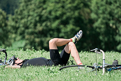 Racing cyclist takes a break in the meadow - p1437m2253427 by Achim Bunz