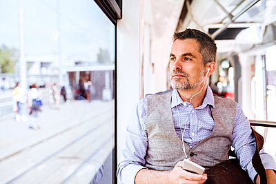 Businessman with smartphone and earphones travelling in tram - p300m1469914 by HalfPoint
