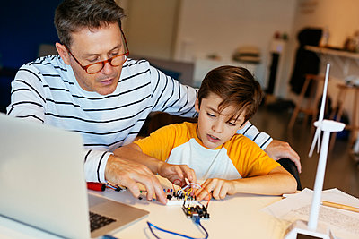 Father and son assembling a construction kit with laptop and wind turbine model - p300m1562673 by Bonninstudio