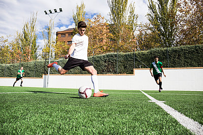 Football player shooting the ball on football field - p300m2083028 by Andrés Benitez