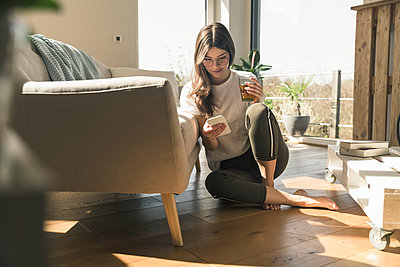 Young woman sitting on the floor at home with drink and cell phone - p300m2104029 by Uwe Umstätter