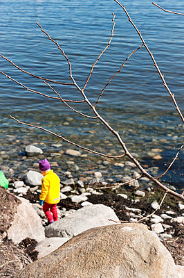 Rocks at water, child on background - p312m1521893 by Rebecca Wallin