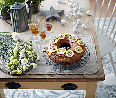 Table with bundt cake, flowers and drinks - p429m1561607 by Debby Lewis-Harrison