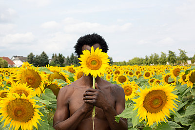 Dark-skinned man with sunflower in front of his face, portrait - p975m2203346 by Hayden Verry