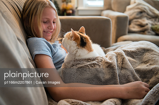 Young girl curled up on sofa looking at white cat - p1166m2207861 by Cavan Images