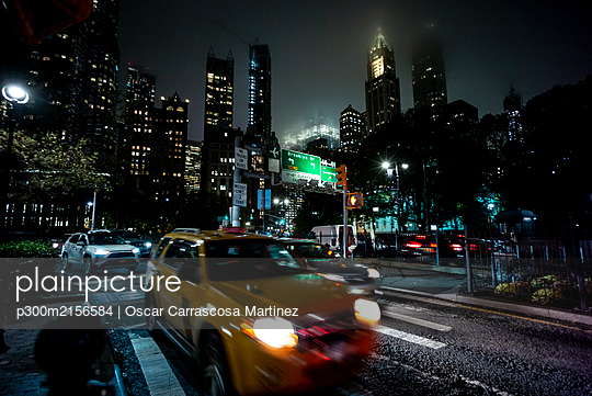 USA, New York, New York City, Traffic on city street at night with tall skyscrapers in background - p300m2156584 by Oscar Carrascosa Martinez