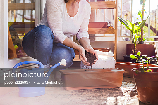 Mid adult woman putting mud in pot while crouching at balcony - p300m2225837 by Flavia Morlachetti