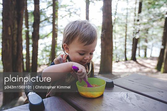 plainpicture - plainpicture p343m1569101 - Toddler eating at picnic ta... - plainpicture/Aurora Photos/Christopher Kimmel