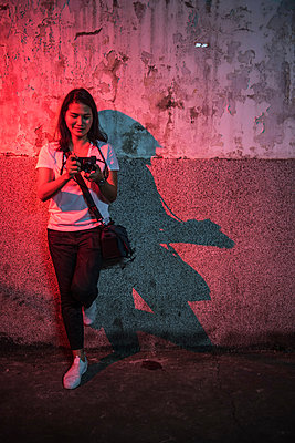 Woman leaning against wall looking at her mirrorless digital camera camera - p429m1561632 by Henn Photography