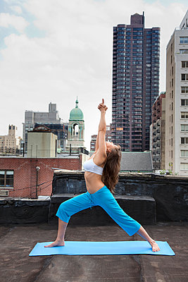 Mixed race woman practicing yoga on rooftop - p555m1478293 by Peter Dressel