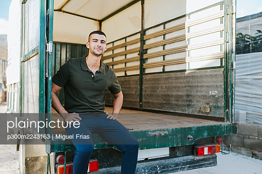 Confident young male farm worker sitting on empty semi-truck outside of organic farm - p300m2243163 by Miguel Frias