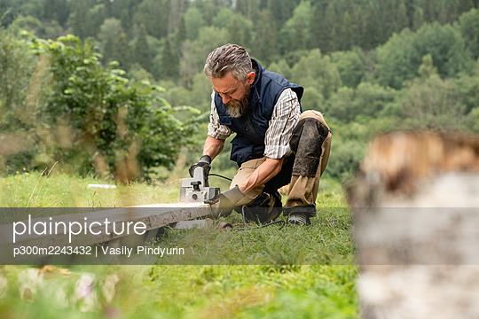 Carpenter sawing plank with circular saw - p300m2243432 by Vasily Pindyurin