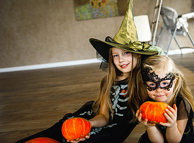 Two Sisters Dressed for Halloween in Skeleton Costumes with Pumpkins - p1166m2147252 by Cavan Images