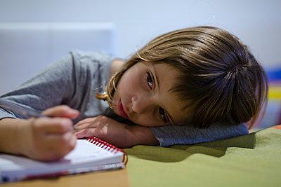 blonde girl doing her homework in the notebook - p1166m2179586 by Cavan Images