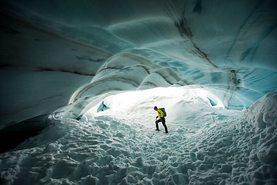 Backpacker explores the inside a glacial ice cave. - p1166m2212634 by Cavan Images
