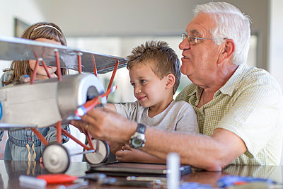 Grandfather and grandchildren building up a model airplane - p300m1047516f by zerocreatives