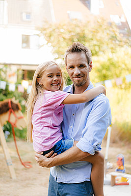 Portrait of smiling father carrying daughter in garden - p300m2059215 by Kniel Synnatzschke