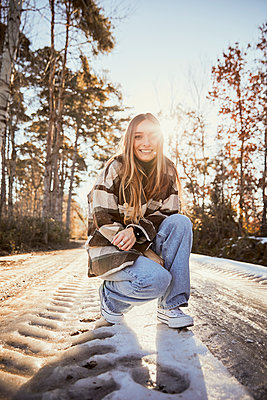 Young woman crouching on snowy road at park during sunny day - p300m2250079 by Aitor Carrera Porté