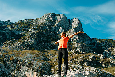 Mid adult woman with arms outstretched standing against mountain at Cares Trail in Picos De Europe National Park, Asturias, Spain - p300m2251008 by David Molina Grande