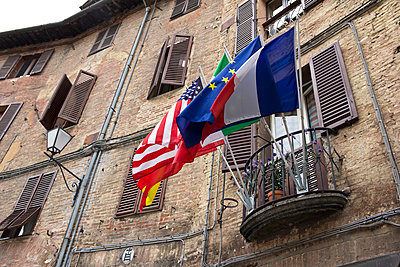 Italy, Tuscany, Siena, Different flags on a balcony - p300m950994f by hollyfotoflash