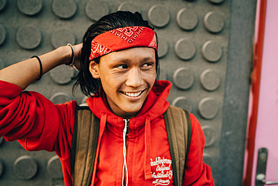 Cheerful young man wearing red bandana while looking away in city - p426m2074852 by Maskot
