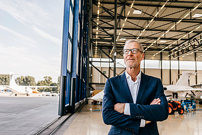 Mature businessman in front of hangar with private jet  - p586m1208507 by Kniel Synnatzschke