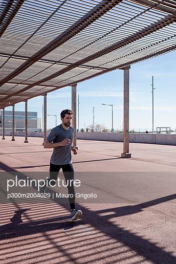 Sportive man runinng under roofing in the city - p300m2004029 von Mauro Grigollo