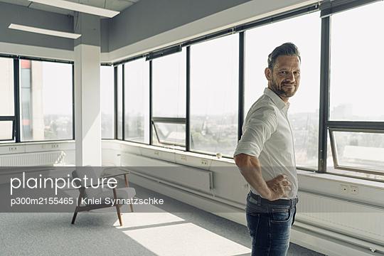 Portrait of confident mature businessman in empty office - p300m2155465 by Kniel Synnatzschke