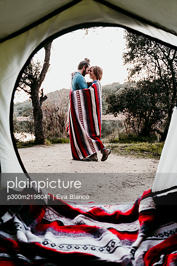 Couple wrapped in a blanket camping at lakeside - p300m2198041 by Eva Blanco