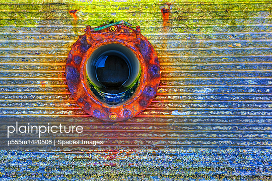Close up of circular window on rusting wall